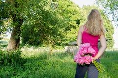 Пион взгляда женщины задний в предпосылке сада руки стоковые фотографии rf