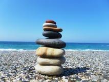 Пирамида камней на пляже против моря и неба Стоковое Изображение RF