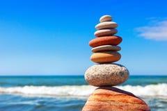 Пирамида пестротканых камешков на предпосылке моря лета Стоковые Изображения RF
