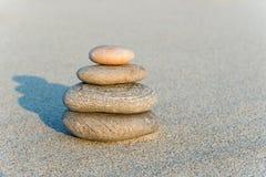 Пирамида из камней на сером песке Стоковое Фото