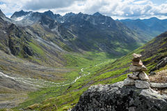 Пирамида из камней на утесе обозревая массивнейший ледник высекла долину в t Стоковое Фото