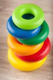 Пирамида колец игрушки пластичных красочных на таблице Стоковое Фото