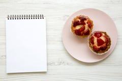 Пироги плавленого сыра клубники ванильные на розовой плите с тетрадью, взгляд сверху стоковые фото