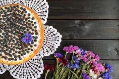 Пирог голубики с букетом cornflowers на черном деревянном ба Стоковая Фотография RF