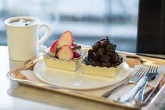 Пирог клубники и пирог шоколада с горячим чаем на таблице Fo Стоковое Изображение RF