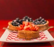 Пирог клубники с пирогами голубики на заднем плане стоковые изображения
