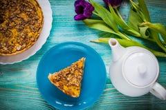 Пирог тыквы на голубой предпосылке с чайником и цветками стоковое фото rf