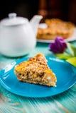 Пирог тыквы на голубой предпосылке с чайником и цветками стоковое фото