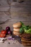 Пирожки говядины бургера, плюшка сезама, свежие овощи, перец, грибы на коричневой бумаге Деревянный космос предпосылки и экземпля Стоковые Изображения RF