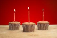 3 пирожного с свечами Стоковое Фото