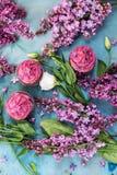 3 пирожного с фиолетовыми сиренью и белой розой на голубой таблице Стоковое Фото