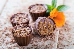 4 пирожного шоколада на белой доске с цветками Стоковая Фотография