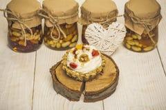 Пирожное, гайки в стеклянных опарниках и сердце на деревянной предпосылке стоковые изображения