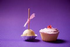 Пирожное и булочка в печенье изолированном на фиолетовой предпосылке Стоковые Фото