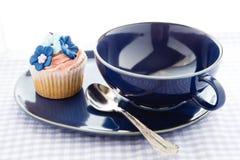 Пирожное и голубая чашка Стоковые Фотографии RF