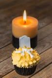 Пирожное и свеча хеллоуина на деревенской таблице Стоковые Изображения RF