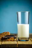 Пирожное и стекло молока на таблице Стоковая Фотография
