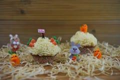 Пирожное при миниатюрный figurine персоны держа знак показывая влюбленность пасху I окруженный украшениями Стоковое фото RF