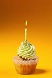 Пирожное при свечка изолированная на померанце Стоковое фото RF