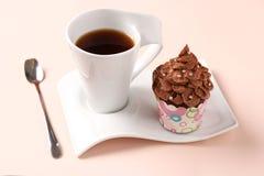Пирожное сливк шоколада и чашка кофе аранжированная на розовой предпосылке стоковые фотографии rf