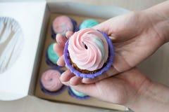 Пирожное с розовой и голубой сливк в руках девушки на предпосылке коробки пирожных Стоковые Фотографии RF
