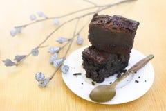 Пирожное шоколада крупного плана в белой плите на деревянном столе с красивым цветком Стоковая Фотография