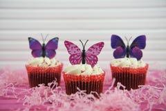 Пирожные вкуса шоколада весеннего времени очень вкусные покрыли с украшениями розовых фиолетовых форм бабочки Стоковое фото RF