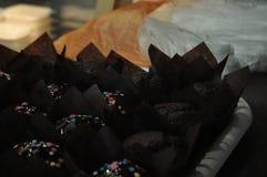 Пирожные в черной упаковочной бумаге стоковые изображения