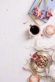 Пирожные кофе и ванили с розовым тюльпаном цветут над белой предпосылкой, взгляд сверху Стоковое фото RF