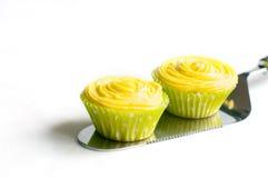 Пирожные с желтой сливк на лопаткоулавливателе торта Стоковая Фотография