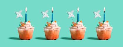 Пирожные с освещенными свечами иллюстрация штока