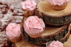 Пирожные с розовой сливк на деревянной предпосылке Стоковое фото RF