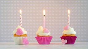 Пирожные с сердцами сливк и сахара и свечой дня рождения Стоковые Изображения RF