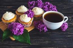 Пирожные с сливк, кофе и цветками Стоковые Фото