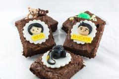 Пирожные с шаржем девушки и мальчика на верхней части Стоковые Изображения