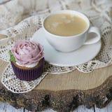 Пирожные украсили со сливками цветки: поднял на деревянную предпосылку с кружевной салфеткой с чашкой кофе карточка праздничная З стоковые изображения