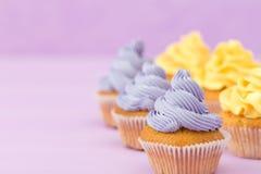 Пирожные украшенные с желтой сливк на фиолетовой пастельной предпосылке для поздравительной открытки с copyscape Стоковые Изображения