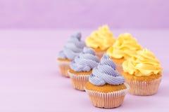 Пирожные украшенные с желтой сливк на фиолетовой пастельной предпосылке для поздравительной открытки с copyscape Стоковое Изображение