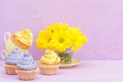 Пирожные украшенные с желтыми и фиолетовыми сливк и хризантемами на фиолетовой пастельной предпосылке для поздравительной открытк Стоковые Фото
