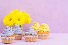 Пирожные украшенные с желтыми и фиолетовыми сливк и хризантемами на фиолетовой пастельной предпосылке для поздравительной открытк Стоковое Изображение RF