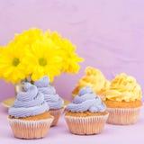 Пирожные украшенные с желтыми и фиолетовыми сливк и хризантемами на фиолетовой пастельной предпосылке для поздравительной открытк Стоковое фото RF