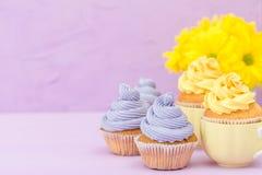 Пирожные украшенные с желтыми и фиолетовыми сливк и хризантемами на фиолетовой пастельной предпосылке для поздравительной открытк Стоковое Фото