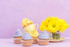 Пирожные украшенные с желтыми и фиолетовыми сливк и хризантемами на фиолетовой пастельной предпосылке для поздравительной открытк Стоковые Фотографии RF