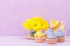 Пирожные украшенные с желтыми и фиолетовыми сливк и хризантемами на фиолетовой пастельной предпосылке для поздравительной открытк Стоковое Изображение