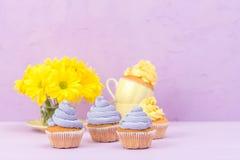 Пирожные украшенные с желтыми и фиолетовыми сливк и хризантемами на фиолетовой пастельной предпосылке для поздравительной открытк Стоковая Фотография
