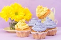 Пирожные украшенные с желтыми и фиолетовыми сливк и хризантемами на фиолетовой пастельной предпосылке для поздравительной открытк Стоковые Изображения