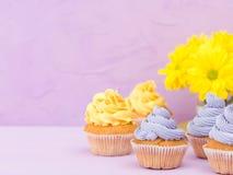 Пирожные украшенные с желтыми и фиолетовыми сливк и хризантемами на фиолетовой пастельной предпосылке для поздравительной открытк Стоковые Изображения RF
