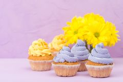 Пирожные украшенные с желтыми и фиолетовыми сливк и хризантемами на фиолетовой пастельной предпосылке для поздравительной открытк Стоковая Фотография RF