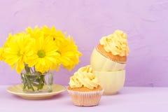 Пирожные украшенные с желтыми сливк и хризантемой на фиолетовой пастельной предпосылке для поздравительной открытки с текстовым у Стоковые Изображения RF