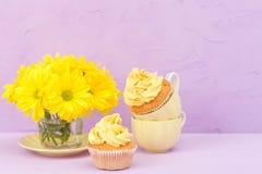 Пирожные украшенные с желтыми сливк и хризантемой на фиолетовой пастельной предпосылке для поздравительной открытки с текстовым у Стоковые Фотографии RF